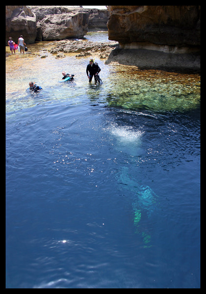 Divers go into a world famous diving spot. Blue Hole under the Azure Window.