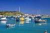 Beautiful afternoon boat reflections on turquoise water in Marsaxlokk Harbor, Malta