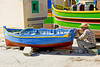 Man painting his colorful boat in Marsaxlokk Harbor, Malta