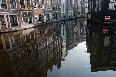 Buildings reflected on the water of the canal - Amsterdam, Netherlands