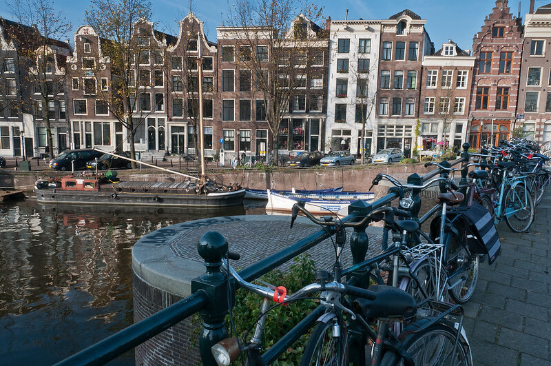 Parked bikes on bridge with view of the canal - Amsterdam, Netherlands
