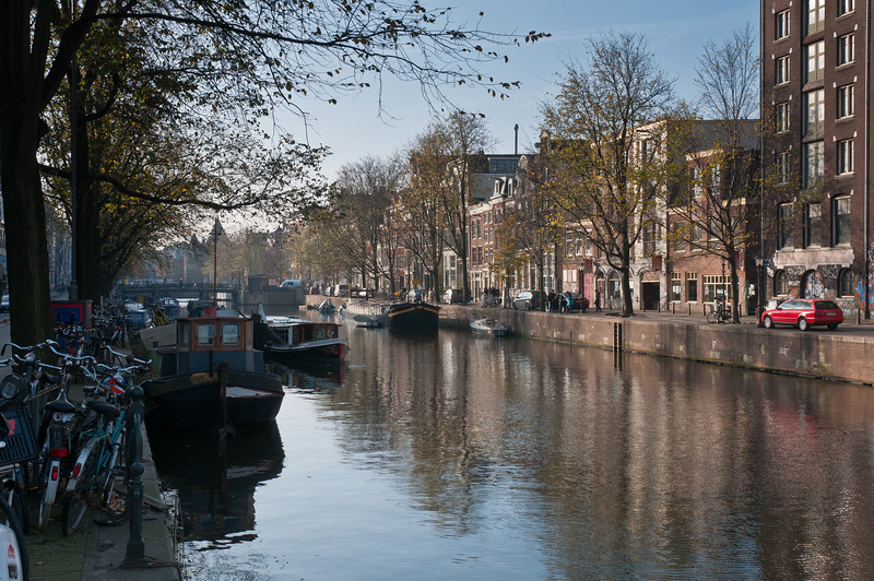 Small boats cruising the canal in Amsterdam, Netherlands