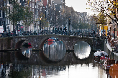 Iconic arched Amsterdam bridge over a canal with parked bikes - Amsterdam, Netherlands