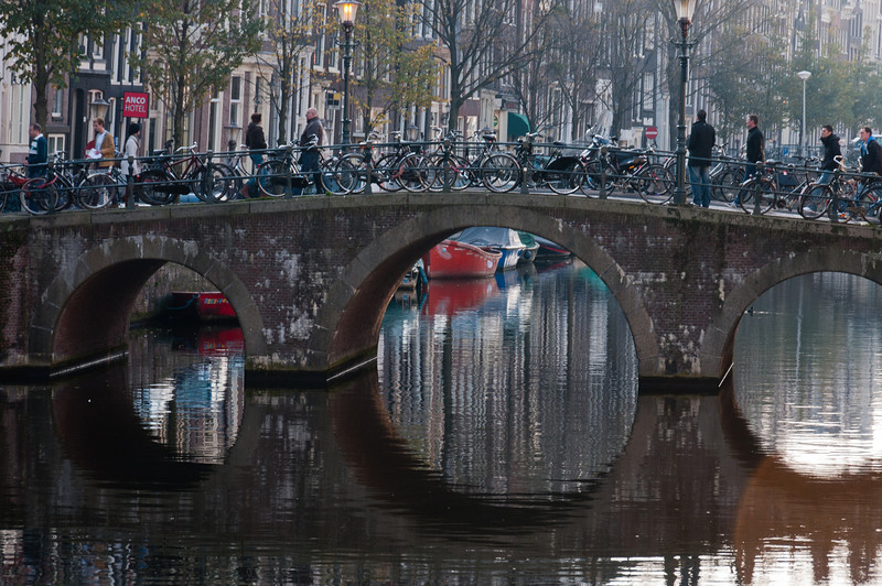 Iconic arch bridge over canal wiht bike parking - Amsterdam, Netherlands