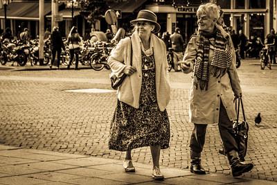 Touching street life scene showing two old Ladies enjoying Nieuwmarkt square.