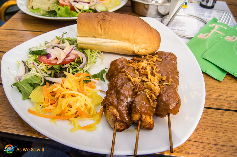 A platter of chicken satay smothered in sauce, two salads and half of a small baguette. Typical dutch food.
