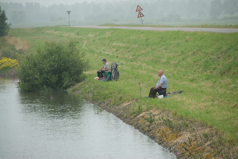 Two men fishing at a river in Kinderdijk, Netherlands