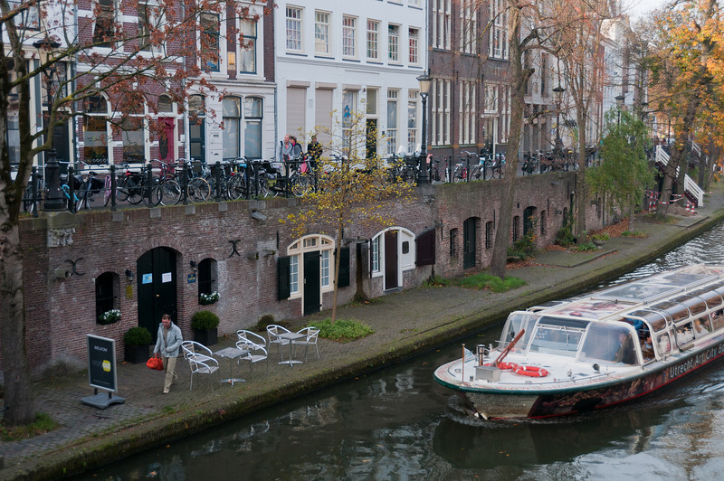 Small boat cruising by Oudegracht in Utrecht, Netherlands
