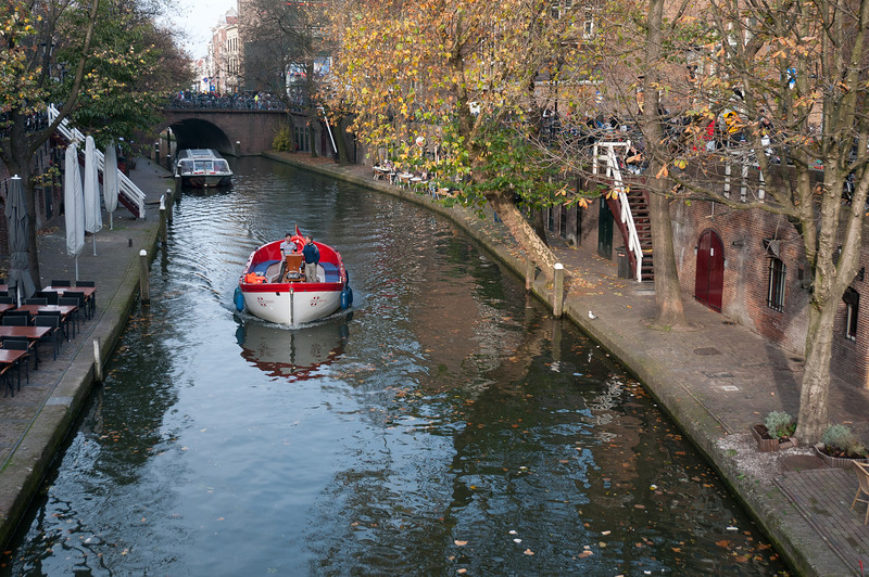 Solitary boat cruising the Oudegracht in Utrecht, Netherlands