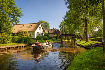 Tourists on a boat in the village of Giethoorn, Netherlands