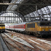 Railion 1615 sits under the roof of Amsterdam Central with the empty stock from a CityNightLine.