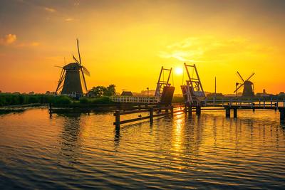 Sunset above a historic drawbridge and old windmills in Kinderdijk, Netherlands
