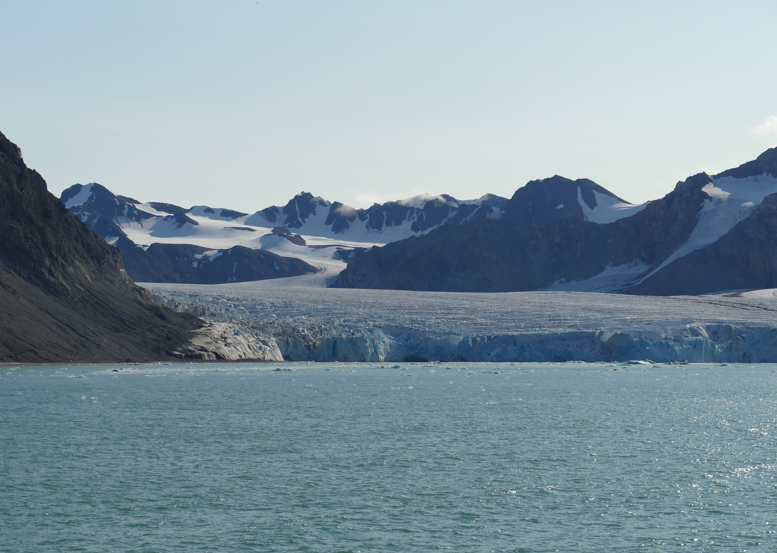 14th July Glacier travels into the sea, surrounded by a mountainous landscape.