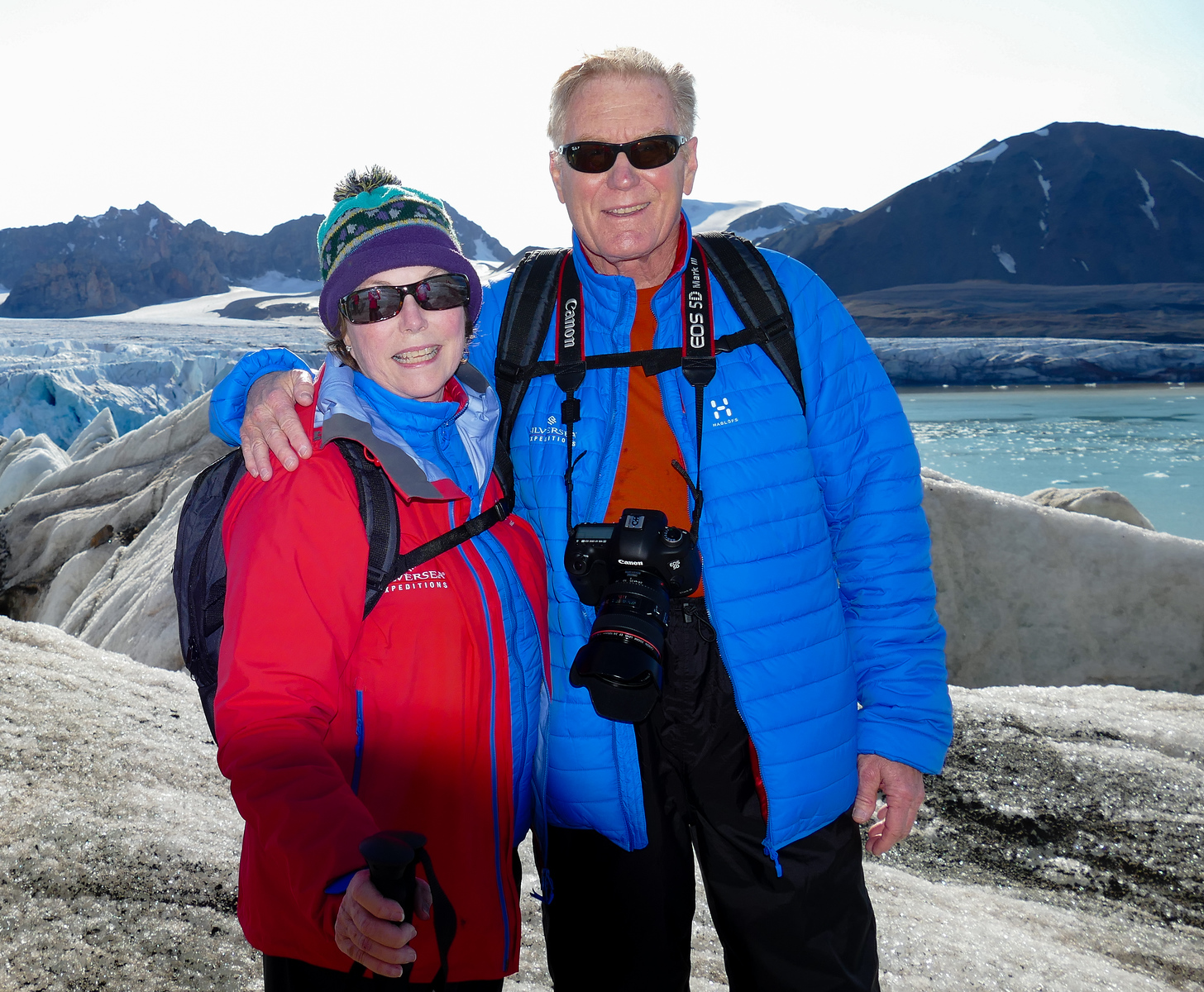 Woman wearing a red jacket and man wearing blue jacket on a glacier hike.
