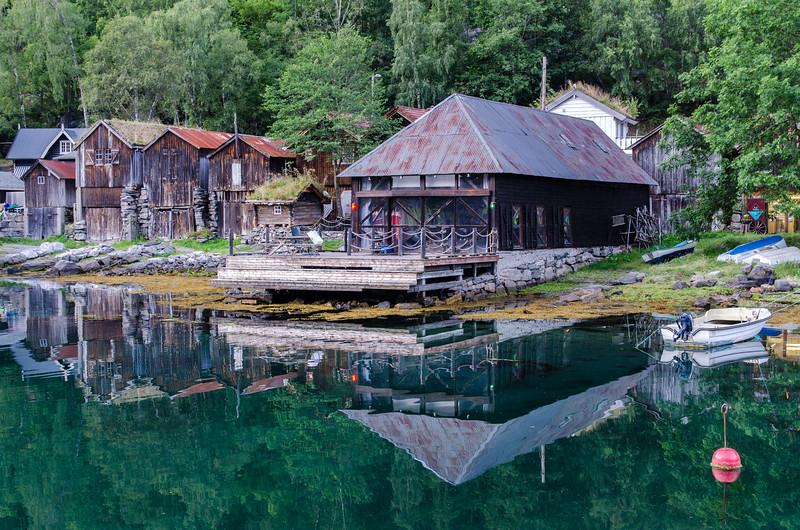 Old fishing shacks on the glass-like Geirangerfjord.