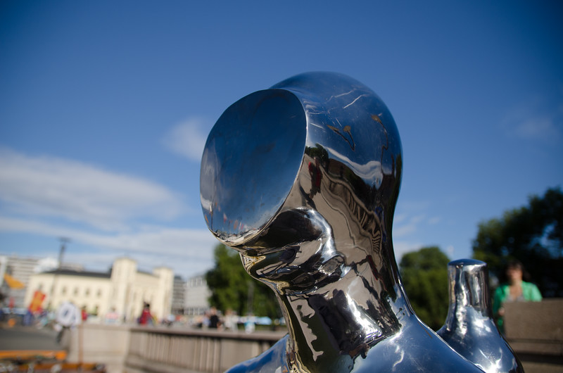 "A close-up of the ""Dykkaren"" statue, a silver scuba diver. It was created by sculptor Ola Enstad."