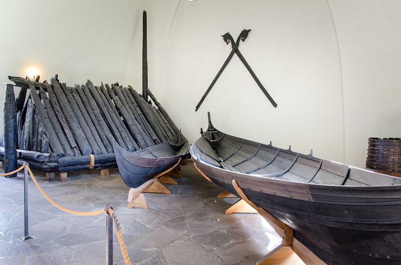 On the left is the burial chamber from the Gokstad Ship. Two smaller boats and a pair of verge boards (on the wall) for a viking tent. This is all from the Gokstad find.