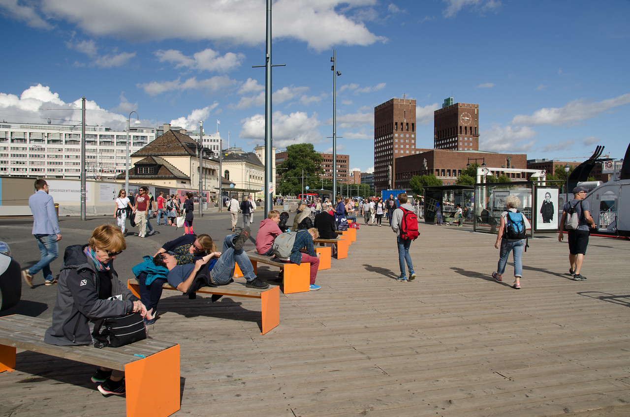 People enjoying a sunny day, Oslo City Hall in the background.