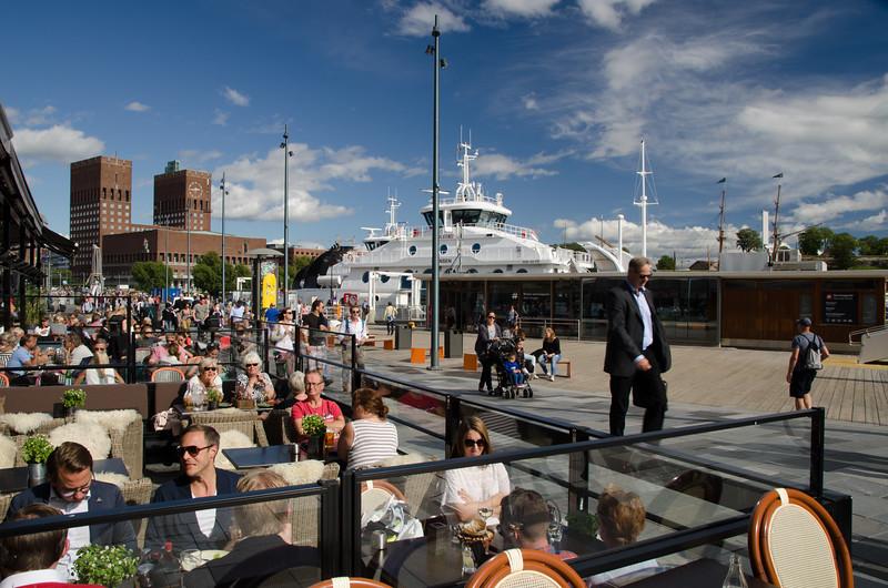 People enjoying cafes on the Oslo waterfront.