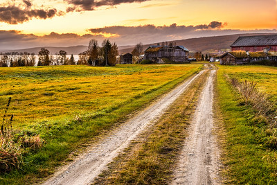 Wooden barn with farmhouse at sunset in Norway