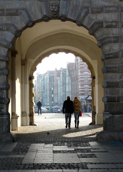 A couple walks through an arched wall onto Long Market Street in Old Town, Gdansk, Poland