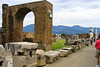 Ancient stones, columns, and pillars line a path in Pompeii
