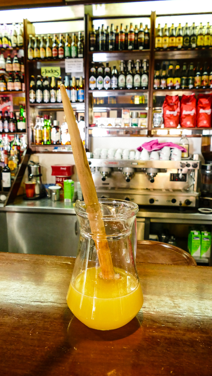 A glass of yellow poncha with a cinnamon stick stirrer.