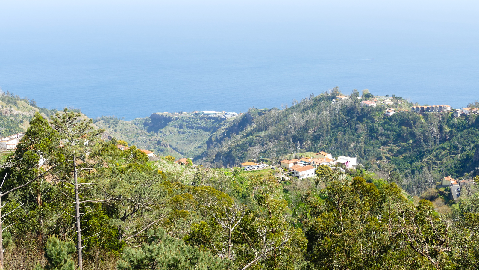 Hillside overlooking a village with the Atlantic Ocean in the background