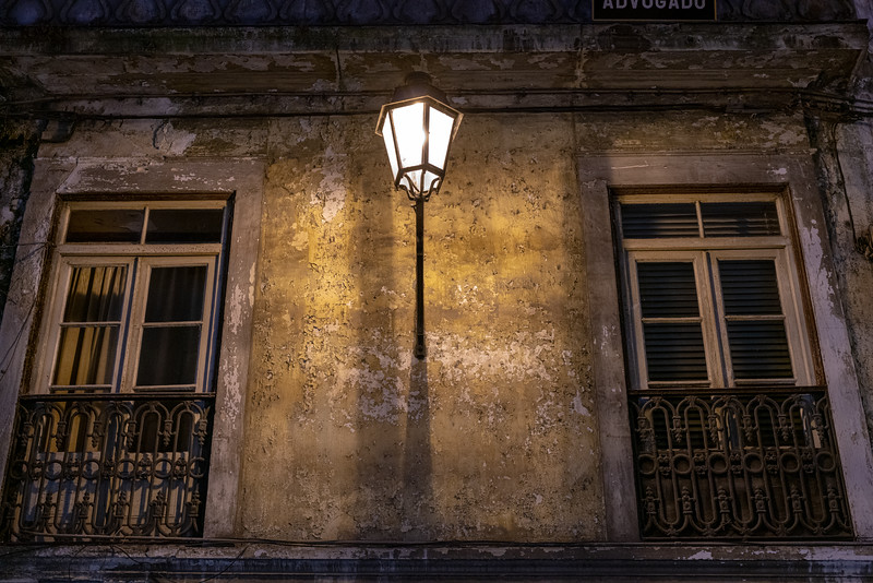 A lamp on a faded but still beautiful building in old Coimbra.