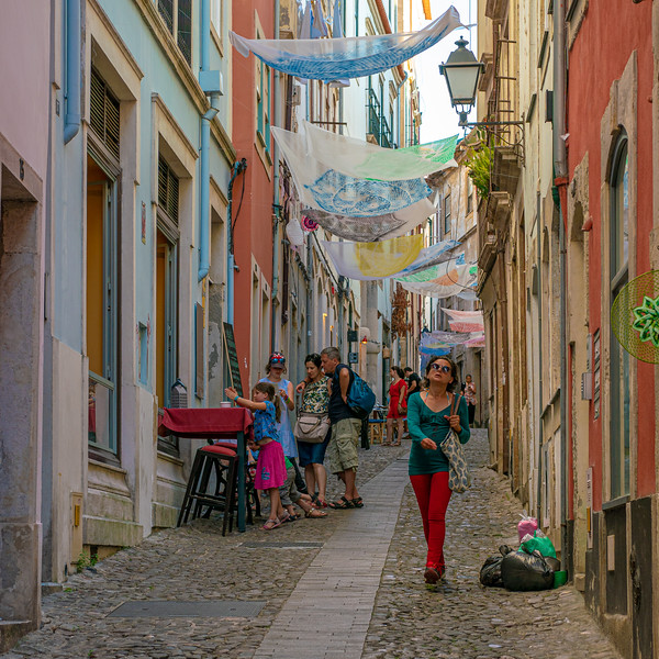 A woman strides along a narrow street near Coimbra's Old Cathedral.