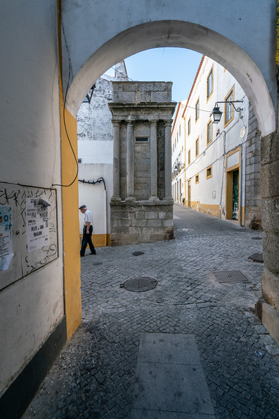 An old man walks alone in Evora.