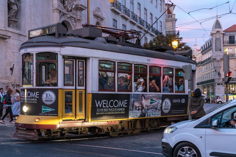 A tram passes the Praça Luís de Camões.
