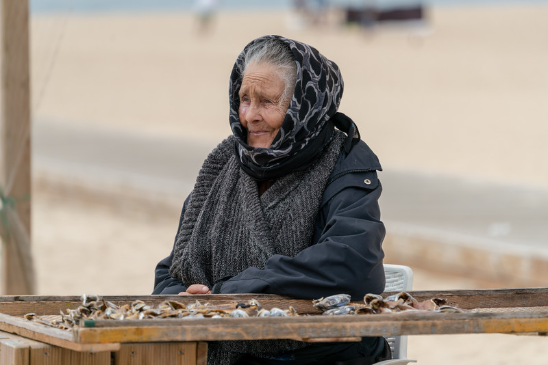 This woman is most likely the widow of a fisherman. She is selling dried fish on the beach.