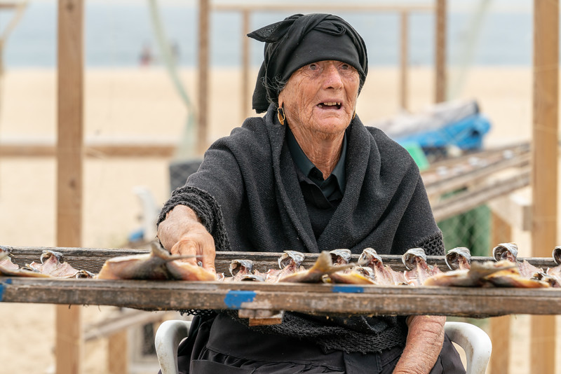 Old widow selling dried fish on the beach.