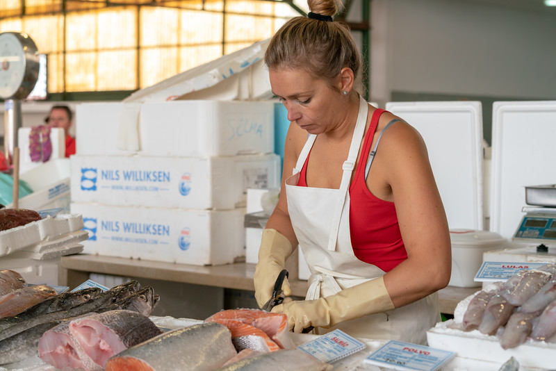A young lady cutting up fish.