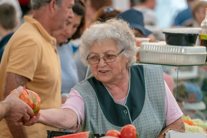 A rosy cheeked lady selling produce in the market in Nazare.