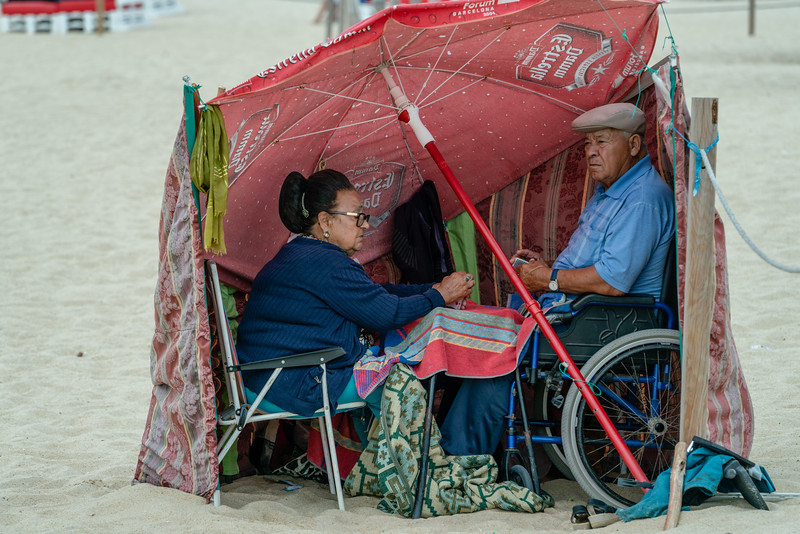 Old couple enjoying a chilly August day at the beach in Nazare.
