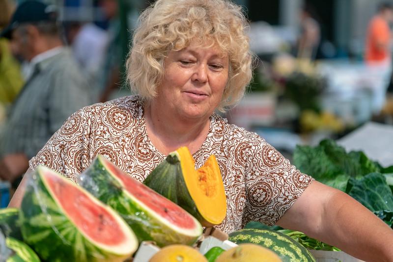 Woman selling mellons and pumpkins.