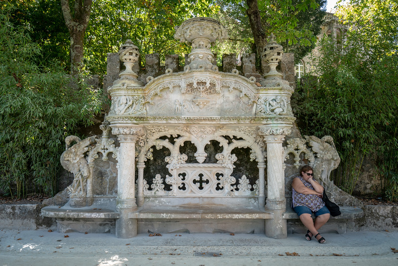 A woman takes a break at an elaborate bench between the chapel and the palace.
