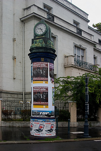 <center>Street Clock   <br><br>Budapest, Hungary   <br><br>No, I don't have a clock fetish. I just thought this street clock with concert posters screamed of another time period.    </center>