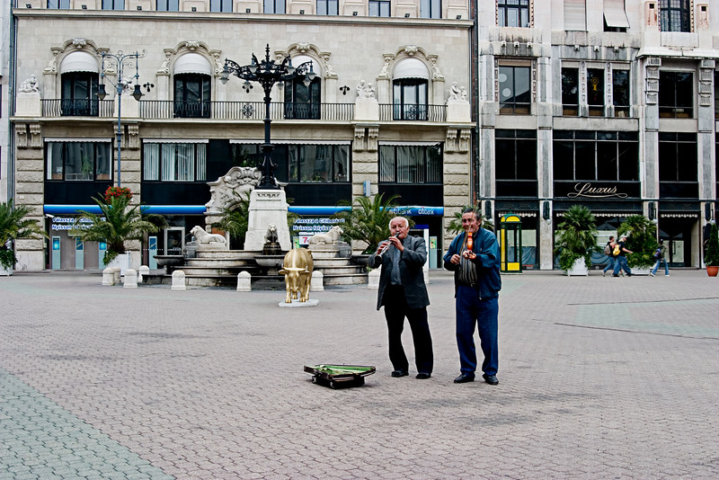<center>Street Musicians   <br><br>Budapest, Hungary   <br><br>Here are a couple of street musicians playing in the central square.    </center>