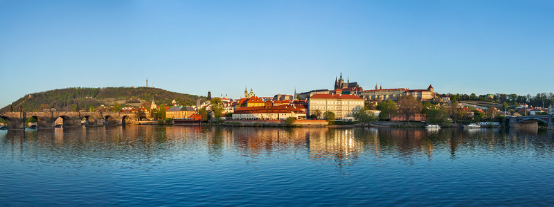 Panorama of Prague: Gradchany (Prague Castle), St. Vitus Cathedral and Charles Bridge over Vltava river on sunset