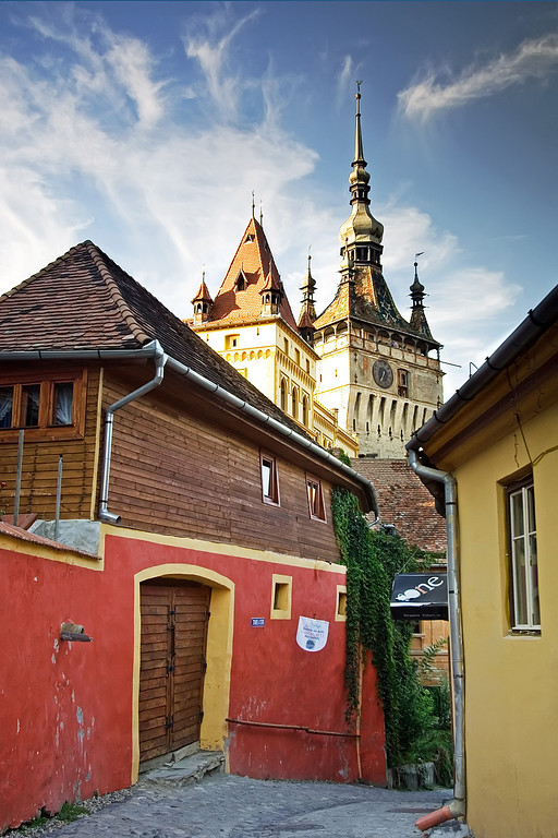 Sighisoara clock tower with traditional buildings in the foregound before streaky blue sky