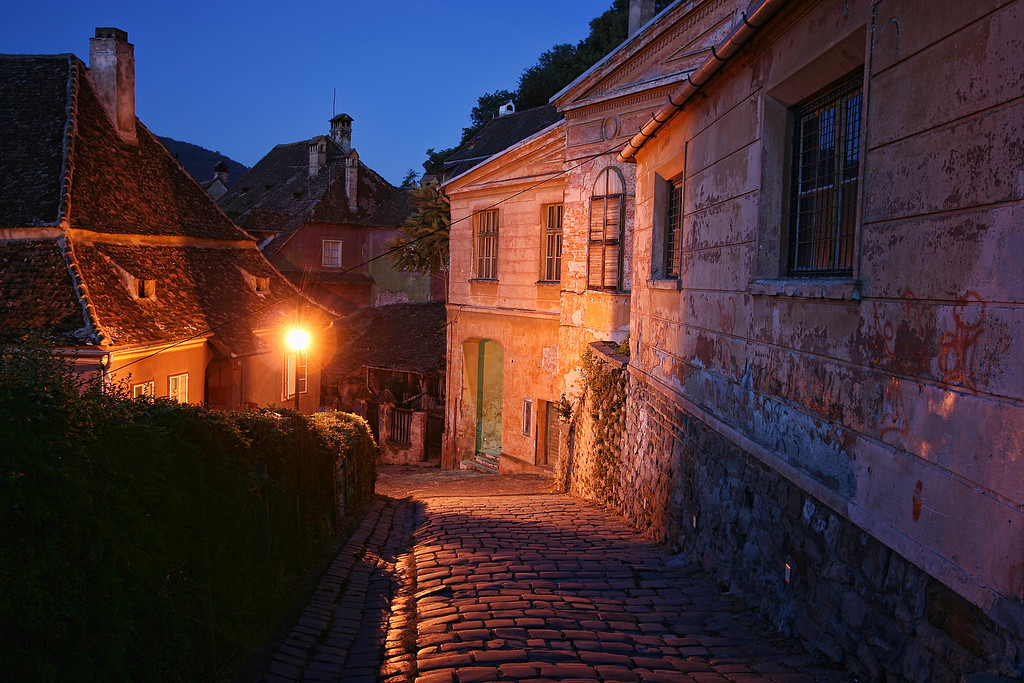 Sighsoara Romania cobbled street and streetlight before sunrise