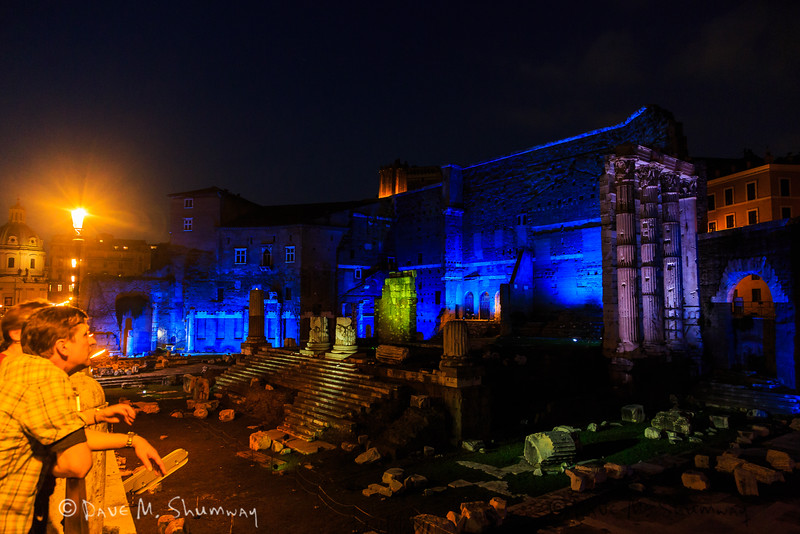 A tourist looks out over Trajan's Forum and Market at night.