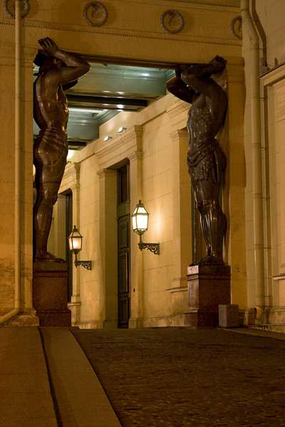 Statues of Atlas, holding up a portico at the State Hermitage Museum at night