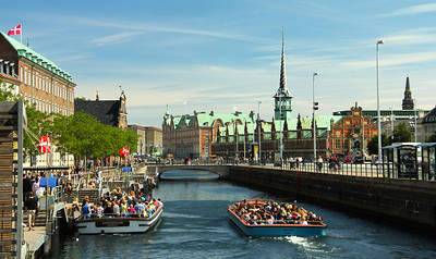 Tourist boats gliding through the inner harbor with the impressive Dutch-Baroque Old Stock Exchange building on the right. ---Copenhagen, Denmark