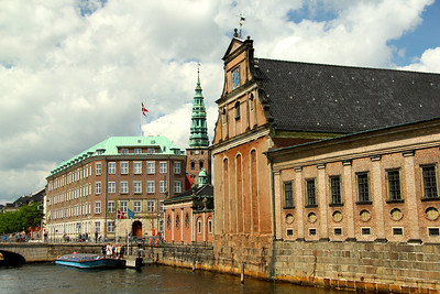 Holmens Kirke (Church of Holmen) on the right with the blue clock dates from the early 1600s  face.  The spire of Nikolaj Church looming behind.  The tower building of Nikolaj Kirke is the only remain of the original church from 1580, as most of the building was destroyed by the catastrophic fires that razed Copenhagen in 1795. ---Copenhagen, Denmark