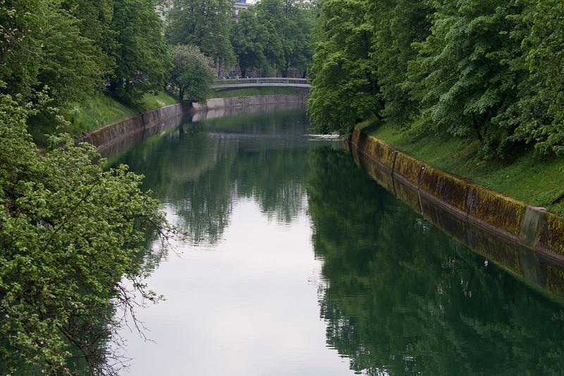 The calm Ljubljanica River flowing through city center in Ljubljana, Slovenia