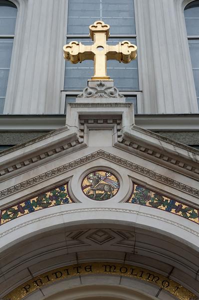 The golden cross by entrance door at The Church of St. John the Baptist in Trnovo, Ljubljana, Slovenia